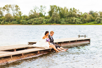 Beautiful bride with groom by a lake. Kiss and hug each other