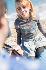 Close-up of blonde girl singing song on beach