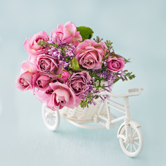 Lilacs and pink roses flowers in a decorative white wooden bicycle on a blue background .Floral gift for a wedding or birthday.