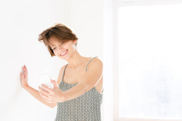 Cheerful attractive young woman making selfie using her mobile phone