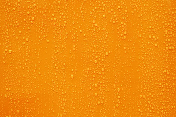Close up water drop on dark orange background.