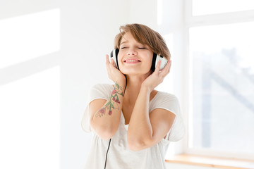 Relaxed happy young woman listening to music using earphones