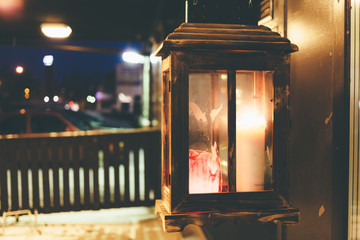 Burning candle in a glass box on the street before an institution at night.