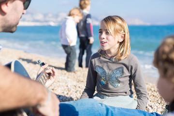 Girl singing while man playing guitar on beach