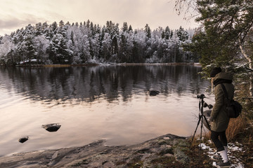 Woman landscape photographer at winter time