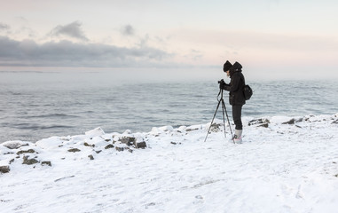 Woman photographer next to lake at winter time