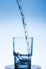 clean water is poured into a glass beaker on a white-blue background