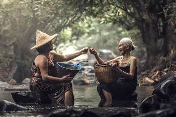 Old Asian woman working in cascade, Thailand