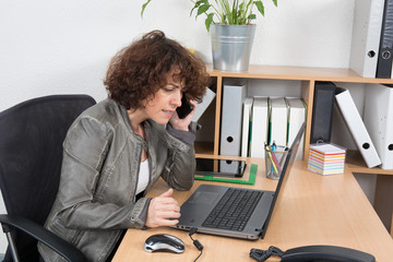 Attractive middle-aged businesswoman pausing in her work