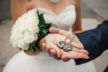 The decorative lock in hands of newlyweds