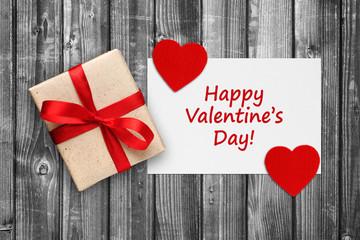Valentines card with gift box and red hearts on black and white wooden background