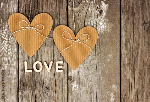 Rustic Heart Shaped Gift Tags With LOVE Wood Letters Hanging Against A Vintage Wooden Background