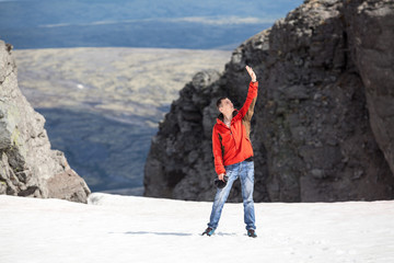 Joyful adult man standing on the mountain pass glacier with hand up to the sky and enjoying the sun