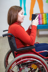 Beautiful Caucasian disabled woman sitting wheel chair and typing message with smartphone, indoor