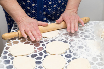sheeting the dough with a rolling pin in the kitchen