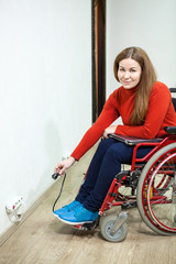 Happy and smiling disabled young woman holding laptop plug while sitting wheelchair indoors