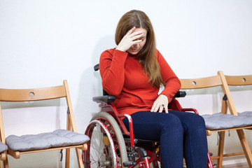 Paralyzed legs sad woman in invalid chair covers her face with hand while sitting between chairs