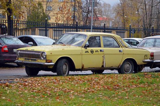 Старый автомобиль такси желтого цвета стоит около осеннего газона