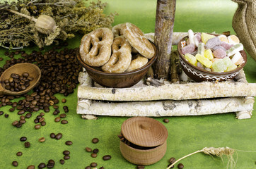 Coffee beans, cookies and fruit candy, herbs, wooden spoon on st