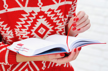 Closeup woman hands with elegant red manicure holding red diary open
