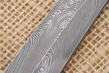 Fragment of the traditional handmade Finnish knife blade with the abstract wave pattern of damascus steel over an old sack background.