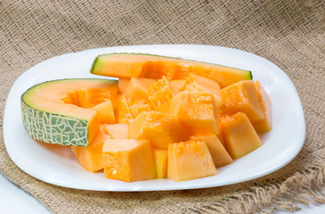 Melons, cantaloupe slices on fabric background