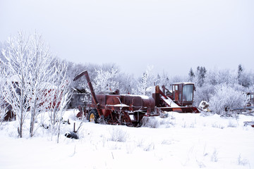 Abandoned and rusted farm machinery surrounded by forest of trees in a winter landscape