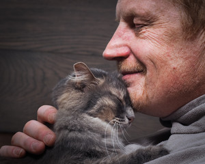 Fototapeta Мужчина и кот - два профиля. Морда кота и лицо мужчины. Мужчина в морщинах. Кот и хозяин улыбаются. Кошка ласково прижимается. Любовь кошки и человека. Отношения, ласка. Фон - деревянная доска obraz