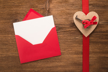 Red envelope with heart on a wooden background