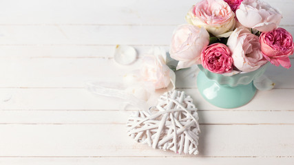 Pastel roses in turquoise vase  and decorative heart on white wo