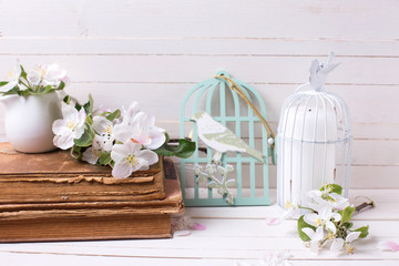Apple blossom,  old books and candle in decorative bird cage on