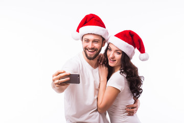 Christmas young beautiful couple in Santa hats in love taking romantic self portrait selfie photo together with mobile phone smiling happy wearing on white background