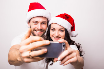 christmas, holidays, technology and people concept - happy couple in santa hats taking selfie picture with smartphone on white background
