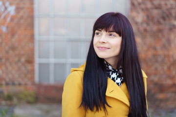 lächelnde frau mit einem gelben mantel