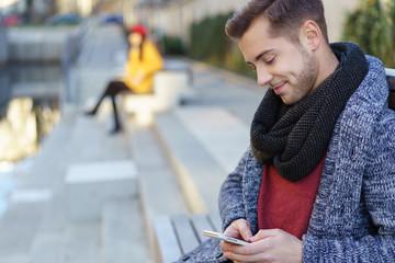 junger mann tippt eine nachricht auf seinem smartphone