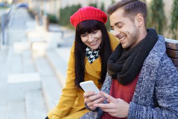 paar sitzt in der stadt und schaut lächelnd auf ein smartphone