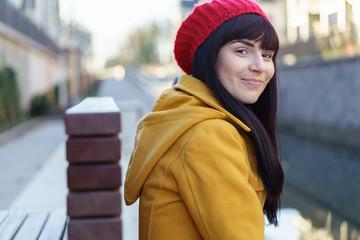 moderne junge frau mit gelber jacke und roter mütze in der stadt