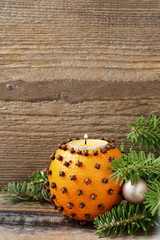 Orange pomander ball with candle on wooden table