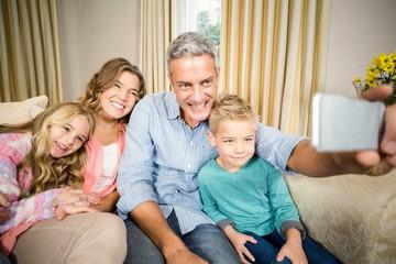 Happy family taking selfie on the sofa