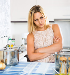 Tired woman leaning her elbows at the kitchen