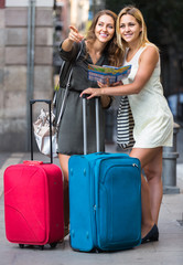 Two women with baggage checking route outdoors