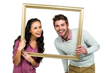 Portrait of happy couple holding picture frame