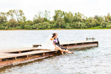 wedding couple  on the pier near big lake