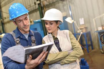 Metal worker showing machine room to apprentice