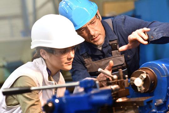 Metal worker teaching trainee on machine use
