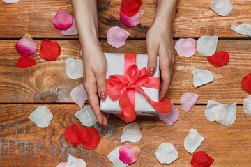 Valentines Day gift and Female hands on wooden background with petals