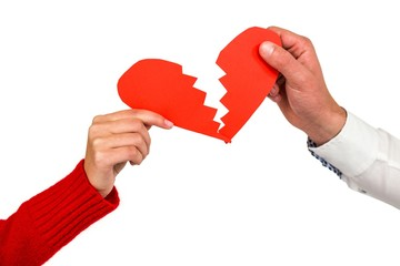 Cropped hands of couple holding cracked red heart shape