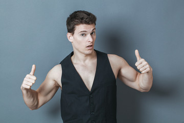 optimism concept - arrogant 20s sporty man with bare chest showing his muscles, studio grey background..