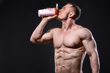 Athlete man drinking protein over dark background