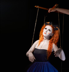 Red-haired girl stylized like marionette puppet on black background